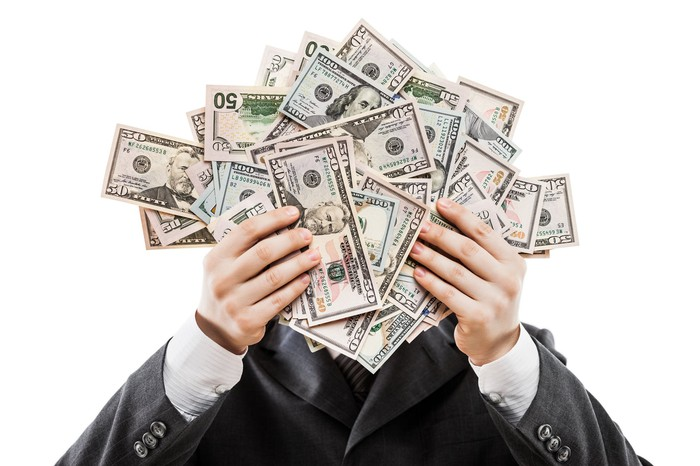Man in a suit holding up a lot of money to hide his face.