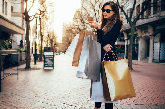 A young woman carrying shopping bags and using a smartphone.