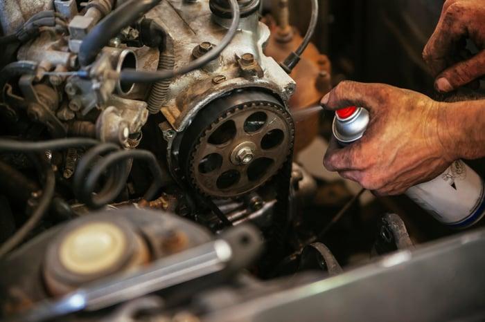 A mechanic sprays lubricant in a car engine.