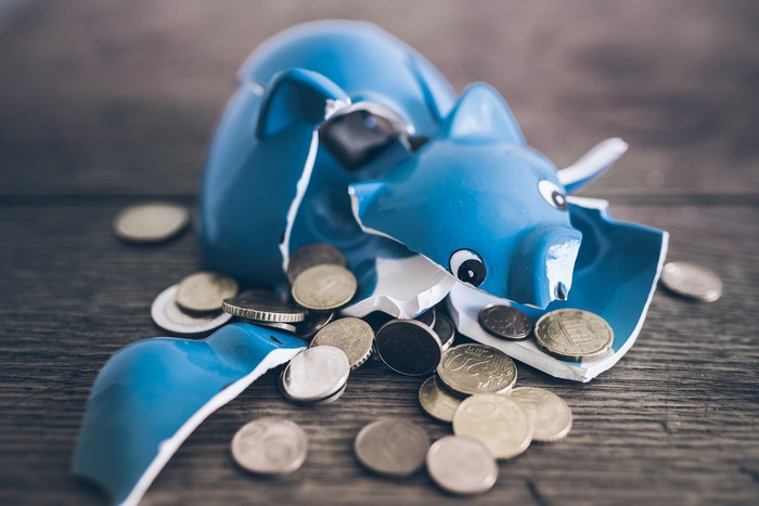 A smashed blue piggy bank with coins falling out.