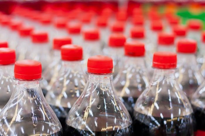 Rows of plastic soda bottles in a bottling plant.