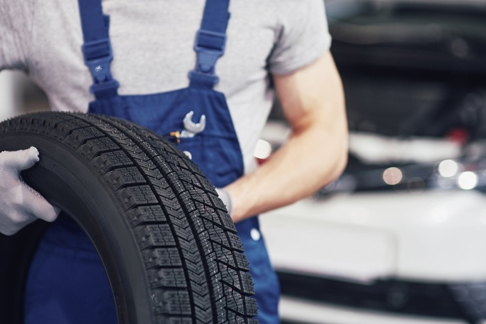 A mechanic holding a spare tire.