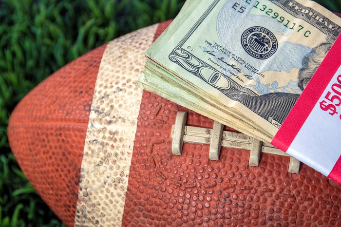 A stack of cash on top of a football.
