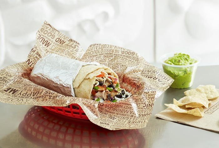 A partially eaten Chipotle burrito shown with a side of guacamole and tortilla chips.