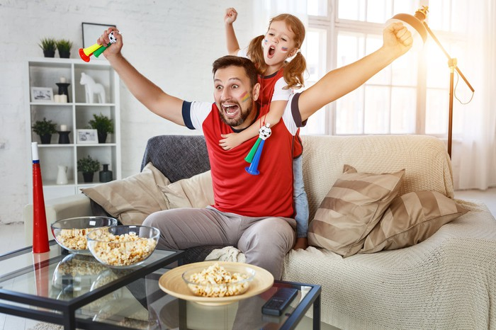A father and his young daughter, with painted faces, cheering on their favorite team from their couch, with popcorn on a table in front of them.