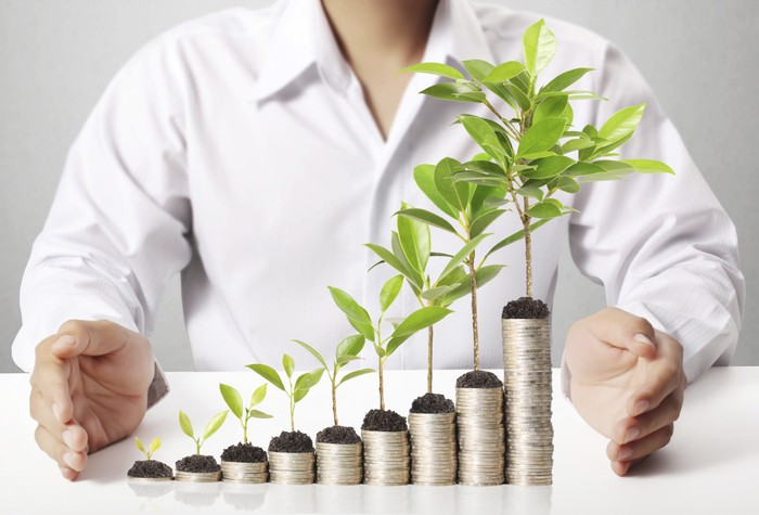 A man standing behind an ascending stack of coins, with progressively larger plants sprouting out of the top of each stack.