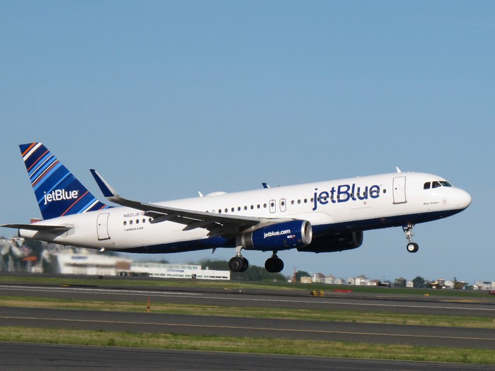 A JetBlue Airways plane about to land on a runway.