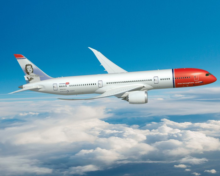 A Norwegian 787-9 flying over clouds.