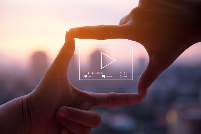 An illustration of a streaming video screen framed by two hands.