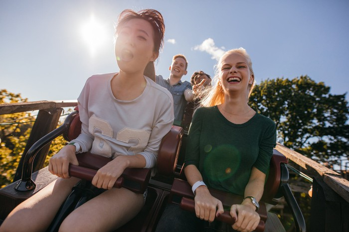 Two young women ride a roller coaster.