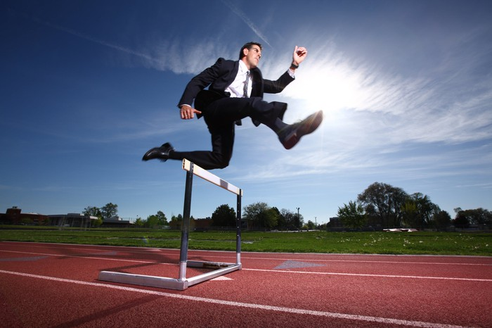 A man in a business suit jumping over a hurdle on a race track.