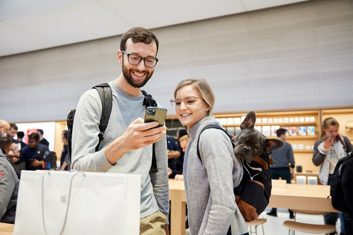 A man and a woman in an Apple Store looking at an iPhone 11 Pro