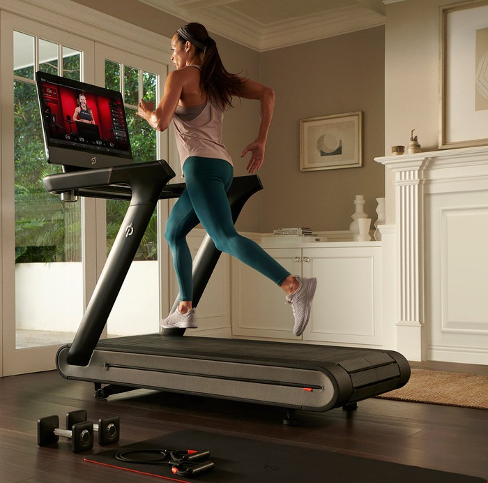 Woman running on a Peloton treadmill