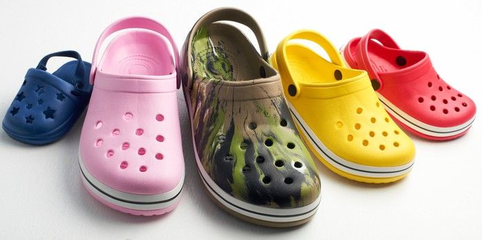 A row of Crocs shoes in various colors and sizes