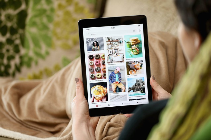 A woman holding an iPad displaying the Pinterest app.