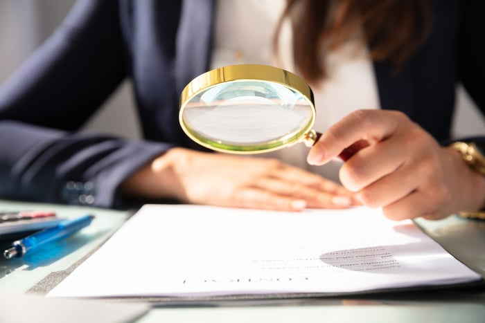 closeup of a magnifying glass held by a woman inspecting a document.