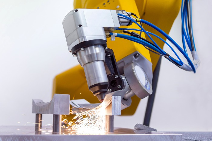 A laser mounted on a robotic arm cutting metal.