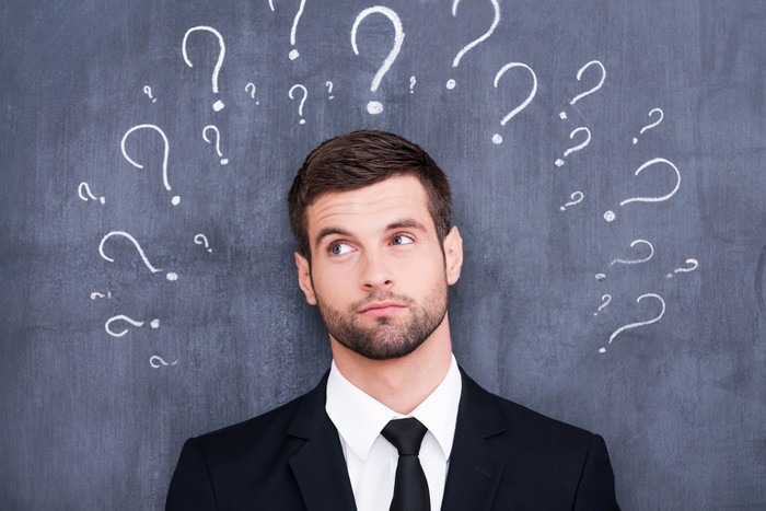 Confused man standing in front of a blackboard with question marks.