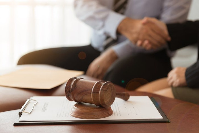 Two people shaking hands next to a legal agreement and a gavel.