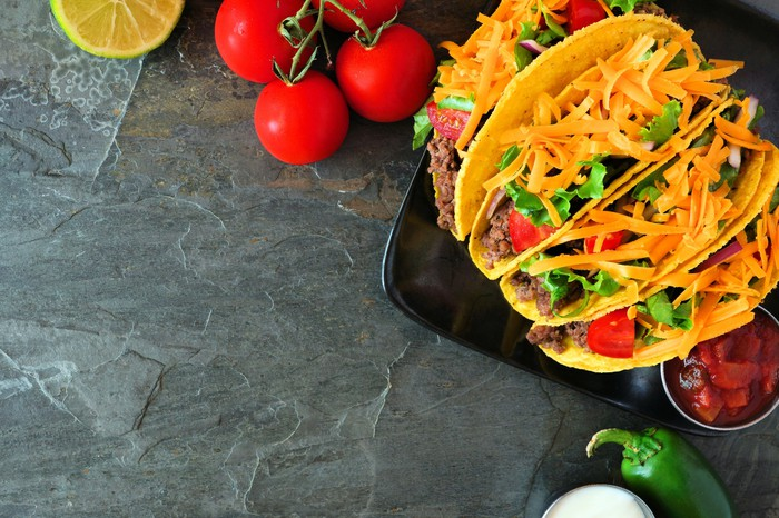 Tacos on a serving board on a gray counter.