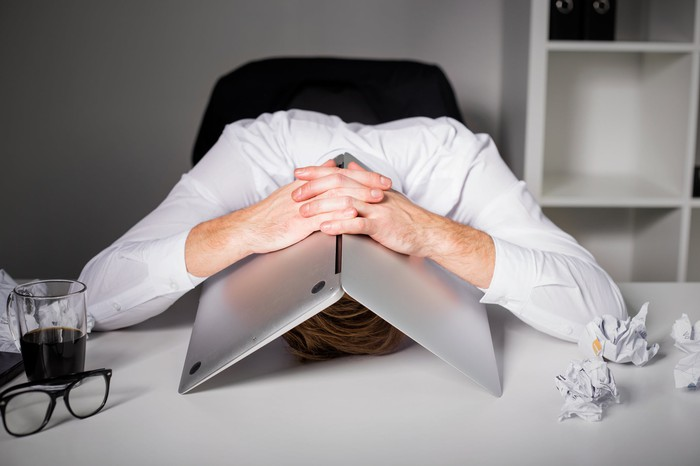 Worker with his head on his desk and his laptop over his head, with his hands crossed on top of the laptop. There are crinkled papers on the desk along with a drink and glasses.