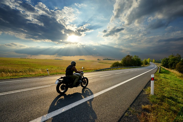 Motorcycle rider on open road.