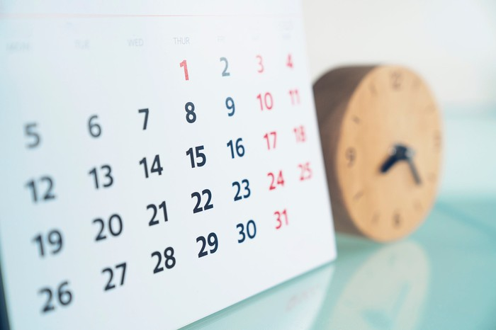 A calendar and an out-of-focus clock on a table.