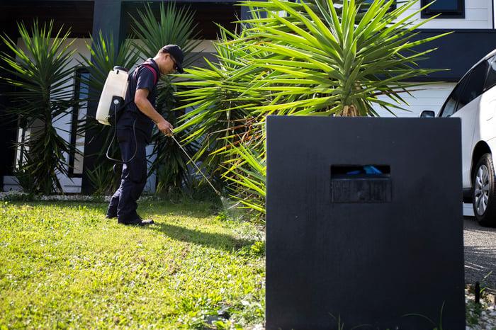 A worker sprays pest control liquid in a yard.