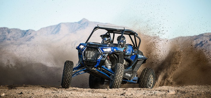 Blue four-wheeler on desert sand with a mountain backdrop.