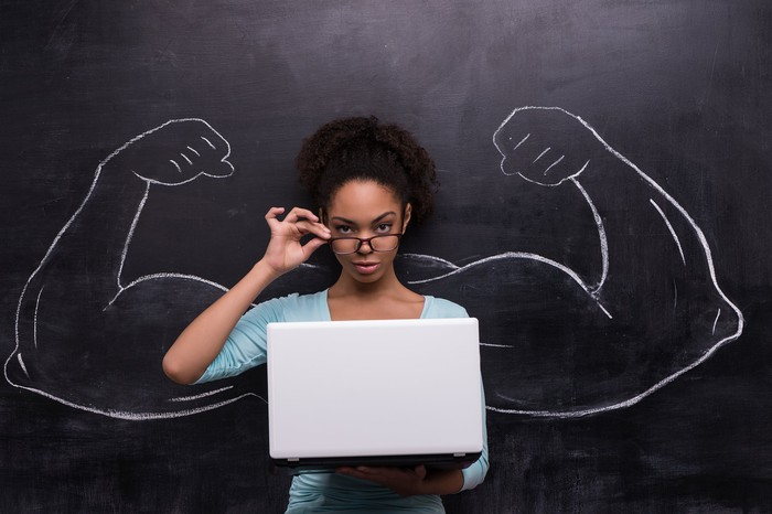 A young woman holding a laptop and her glasses standing in front of a blackboard on which, behind her, are drawn a pair of muscular arms flexing their biceps.