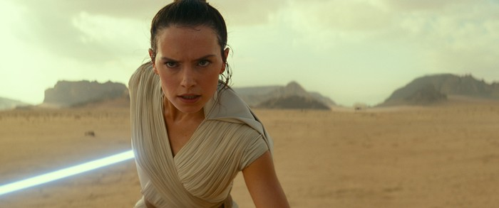 A young woman with a determined look standing in the desert holding a light saber.