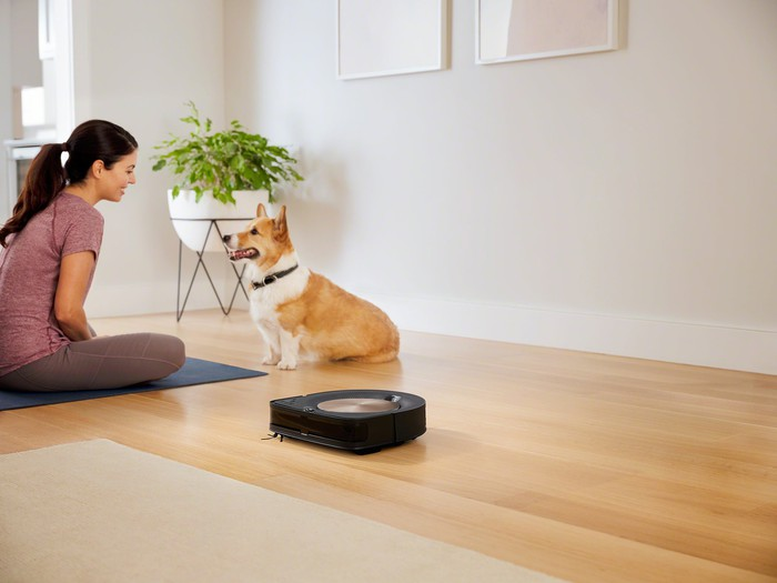 A woman sitting on the floor with a dog, with a robotic vacuum in the foreground.