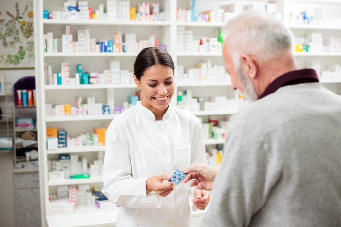 A female pharmacist dispensing medication to an older male customer.