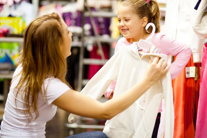 A mother and her young daughter, clothes shopping