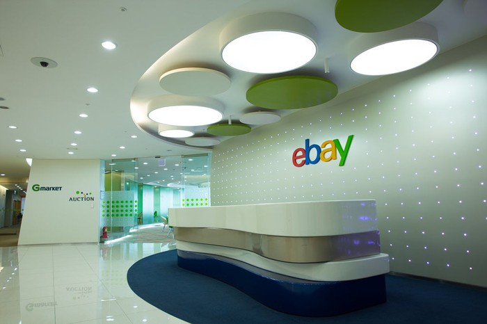 eBay front desk with company logo on wall behind it.
