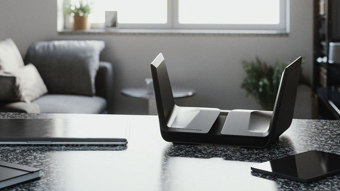 A TIE-fighter-shaped Netgear Nighthawk router sitting on a countertop in a home or office.