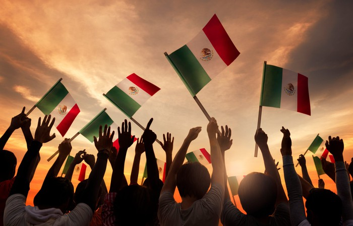 A group of people holding Mexican flags with the sun rising in the background