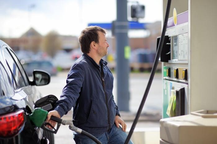 A man pumping gasoline into a car.