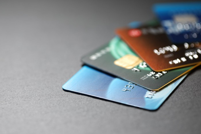 Four credit cards on top of each other on a grey surface.