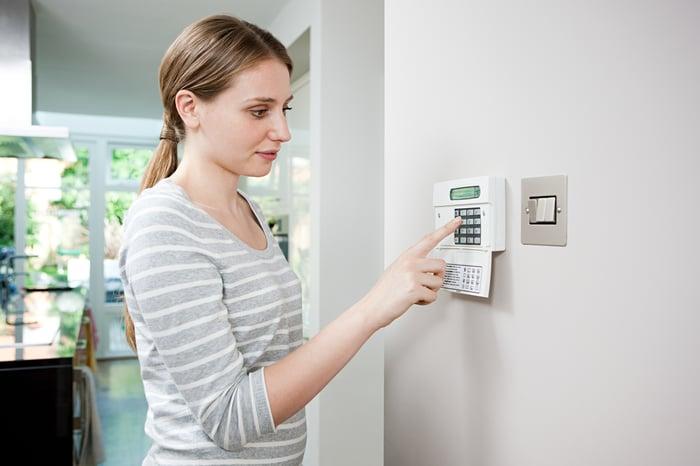 A woman setting a burglar alarm.
