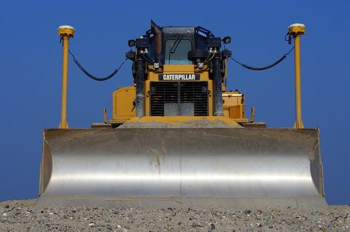 Large bulldozer with metal blade pushing a sand/rock mix.