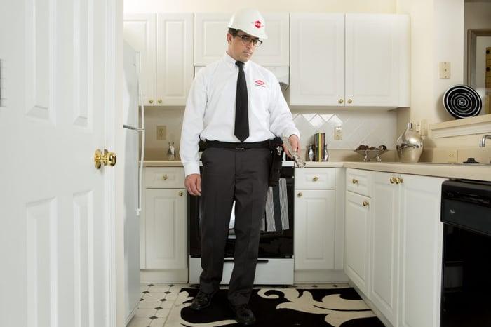 Orkin employee standing in kitchen.