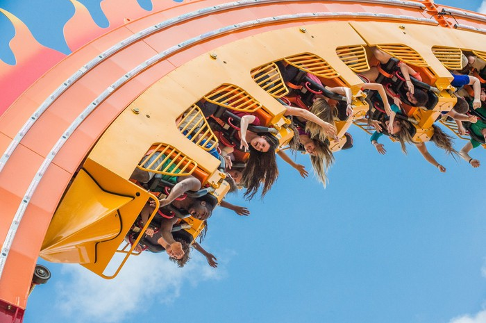 An upside-down roller coaster with riders holding out their hands