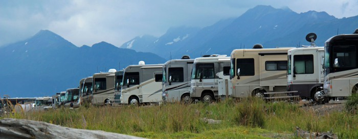 A row of Winnebagos against a mountain background.
