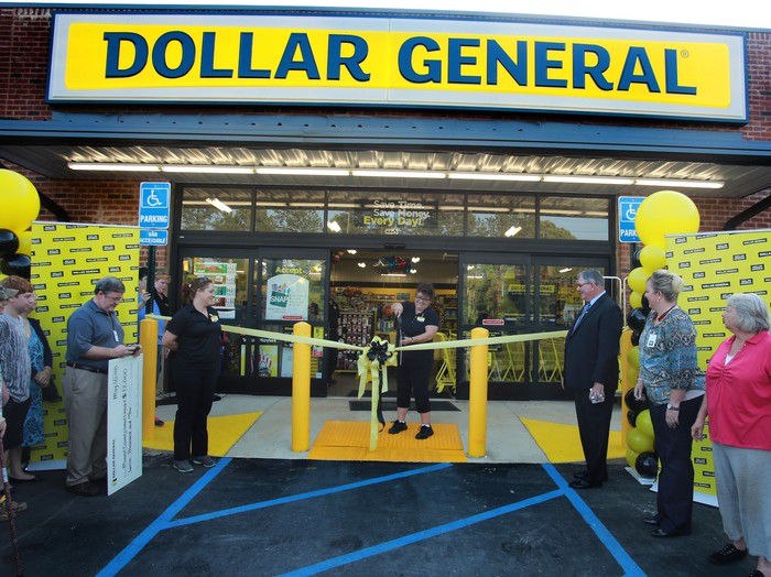 Dollar General store with woman cutting a yellow ribbon as several people watch.