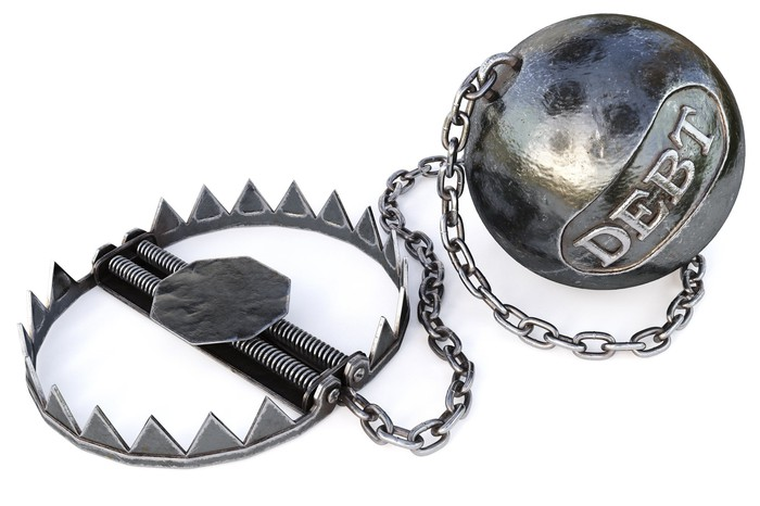 A large weighted ball with the word debt engraved on it that's attached by a chain to a bear trap.