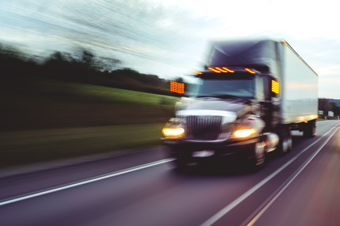A freight truck driving down the highway