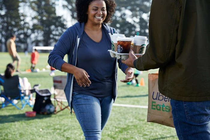 A soccer mom receives a Starbucks delivery at her children's game.