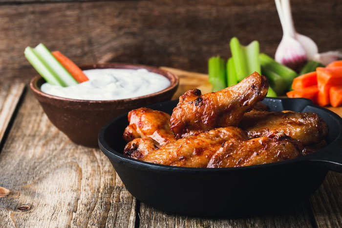 A bowl of chicken wings with ranch dressing and vegetable sticks.