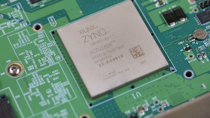 A Xilinx Zynq chip displayed on a green circuit board.